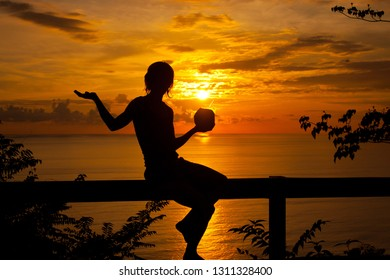 Sexy female silhouette in romantic sunset time on Caribbean coast with coconut drink in her hand