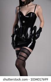 Sexy fetish woman in black latex corset, mini skirt and gloves, studio shot
