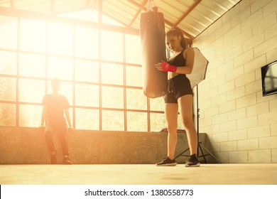Sexy fighter girl in gym with boxing bag, Female boxer resting after punching a boxing bag in gym.