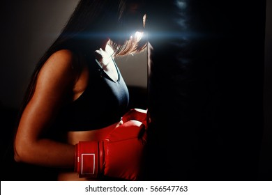sexy fighter girl in gym with boxing bag. Long hair woman fitness model