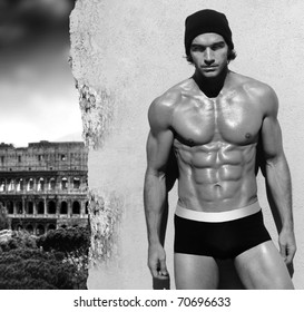 Sexy fine art black and white portrait of a very muscular shirtless male model posing with view of Rome in the background