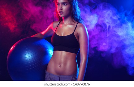 Sexy fit brunette woman holding a fitness ball on blue and violet smoky wave background