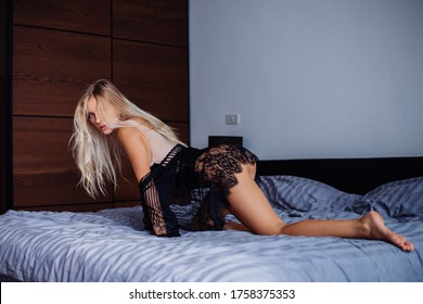 Sexy fit european woman in bedroom at sunrise light in beige body and black transparent lace cape does on bed. Female in stylish home clothes enjoying time at home.