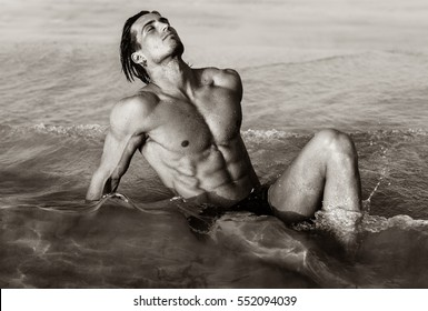 Sexy fit male model lying in the water at the beach.