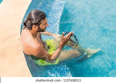 Sexy fit man with goggles relaxing in the swimming pool in a resort