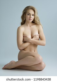 Sexy fit naked woman with healthy clean skin sitting at studio. Beautiful perfect female body of pretty young caucasian girl.