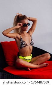 Sexy fit tanned european fashion blogger woman in tiny leopard bikini, neon yellow green waist bag on red pillow sofa, sunset. Accessories and sunglasses. Weight loss motivation, fashion concept.