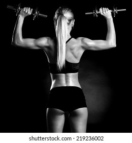 Sexy and fit woman lifting hand weights