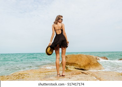 Sexy fit woman on big rocks correct her little black summer dress flying in the wind. View from back. Beauty cute girl on a tropical beach sea ocean shore with large stones. Outdoor summer lifestyle.