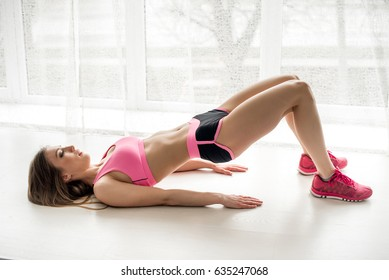 Sexy fitness athlete performs an exercise bridge in the studio.