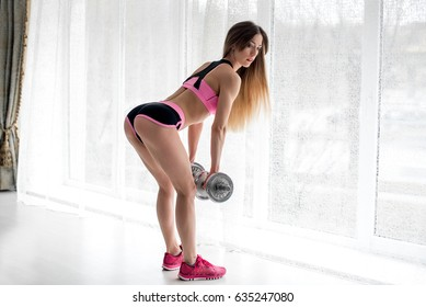 Sexy fitness athlete performs exercises on the buttocks in the studio. Body-building.