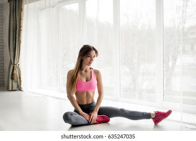 Sexy fitness athlete performs a warm-up before the exercises in the studio.