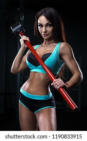 Sexy fitness brunette woman is posing in the gym with the sledgehammer
