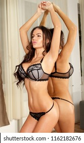 Sexy fitness ethnic lingerie model woman in front of mirror