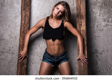 Sexy fitness girl  posing beside a  dirty wall