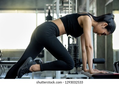 Sexy fitness girl in sport wear doing stretching workout with perfect body in the gym