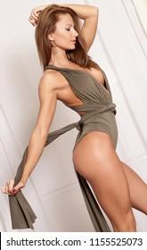 Sexy fitness lingerie model woman in green fashion bodysuit