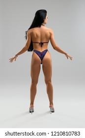 Sexy fitness model in shiny bikini rearview