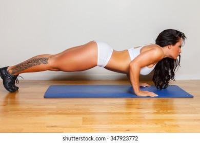 Sexy fitness woman doing push ups on blue fitness mat.