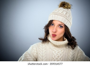 Sexy flirtatious young woman in winter fashion wearing bright red lipstick puckering up her mouth in a pout for a kiss for the camera, head and shoulders over grey