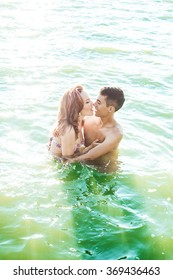 Sexy French kiss in hot water. passionate couple in sunglasses staying in deep sea shore or ocean. perfect body and sporty couple. bodybuilders outdoors