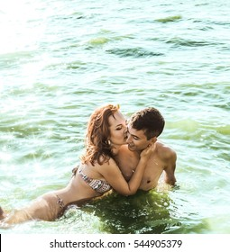 Sexy French kiss in hot water. passionate couple in sunglasses staying in deep sea shore or ocean. perfect body and sporty couple. man and woman outdoors