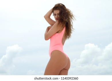 Sexy full figure girl at beach with hair blowing in the wind