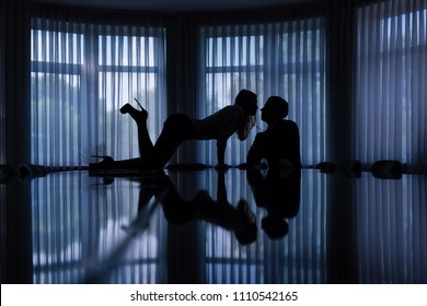 Sexy games of woman and man in dark office