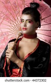 Sexy geisha holding an umbrella. studio shot