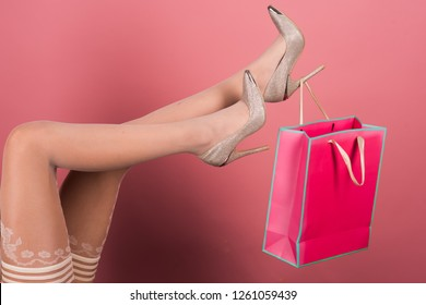 Sexy gift. Christmas gift from a lingerie store or sex shop. Seductive stockings. Sensual female legs with shopping bag present. High heels for ladies. Presents concept