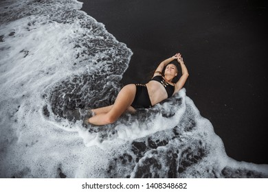 Sexy girl in a bathing suit lying in the waves on the black sand. View from the top.