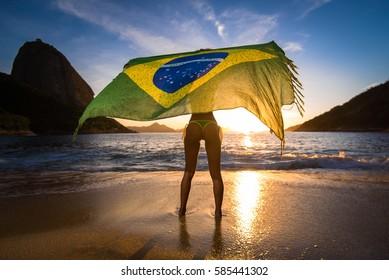 Sexy Girl in Bikini Holding Beach Yoke With Brazilian Flag Waving in the Wind, with the Sugarloaf Mountain View by Sunrise, in Rio de Janeiro