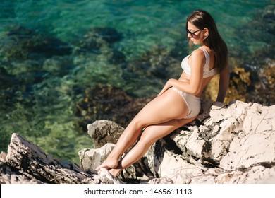 Sexy girl in bikini lying on the rocks. Beautiful lagoon in background. Fashion model sunbathing by the sea