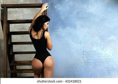 Sexy girl in a black body. Athletic body. Slender graceful girl. Fitness model. Big ass. Girl near the wall. Beautiful girl. Beautiful figure.