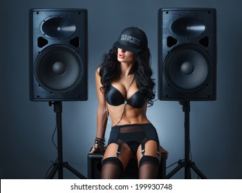 sexy girl in black lingerie and baseball cap sitting on the audio speaker against blue background