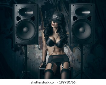 sexy girl in black lingerie and baseball cap sitting on the audio speaker against wall with graffiti