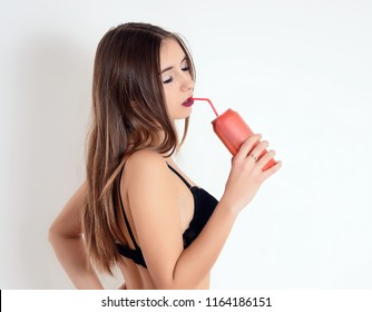 Sexy girl in black lingerie drinking through a straw from a red can