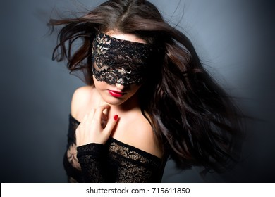 Sexy girl in black lingerie on black background. Erotic photoshoot charming attractive woman with a blindfold mask on her face. Perfect picture and beautiful makeup