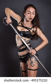 Sexy girl in black lingerie and sword belt on gray background. Gets a sword from a sheath.