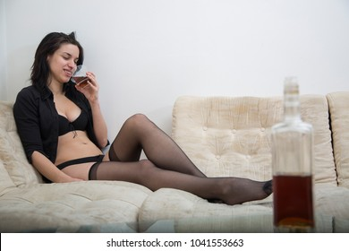 Sexy girl in black provocative lingerie sitting on sofa in apartment and smiling while she drinks alcohol.