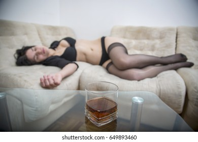 Sexy girl in black provocative lingerie sleeping on sofa in apartment with glass of alcohol on glass transparent table in front of her.