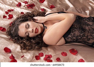 The sexy girl blindly lies on a bed with petals of roses