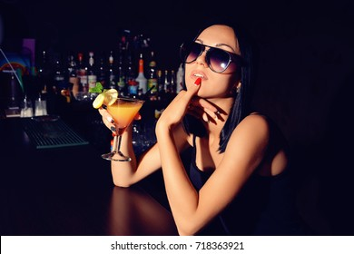 Sexy girl with cocktail sitting at the bar.