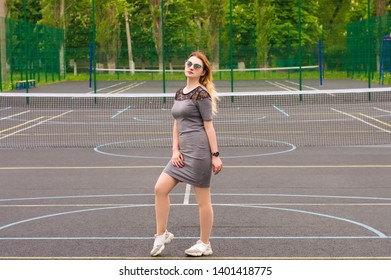 sexy girl in a dress standing on a Sportsground