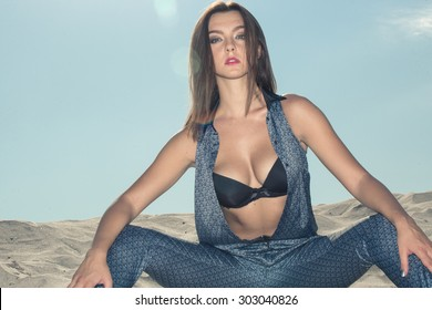 sexy girl dressed in blue overalls and a black bodice, on the sand against the sky