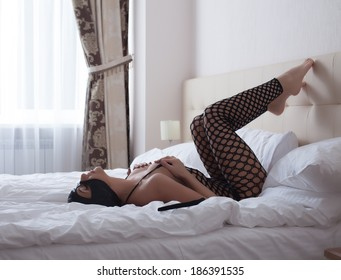 Sexy girl dressed as catwoman lying in bed