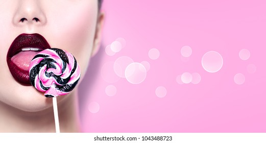 Sexy girl eating lollipop. Beauty Glamour Model woman Licking sweet colorful lollipop candy, on pink background, close-up. Closeup mouth and tongue. Seductive lips, burgundy color lipstick