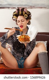 sexy girl eating spaghetti on the couch