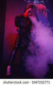 Sexy girl exhales a thick white smoke.smoking fruit flavored e-liquid or e-juice with vaporizer device or e-cig. Modern gadget for smokers.Young pretty woman smoking e-fag wearing black leather jacket