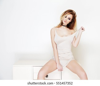 The sexy girl In a fitting dress sits on a curbstone, a tempting look, a beautiful figure, a magnificent breast, the naked shoulder removes from itself, one hand keeps curly hair, all in beige color